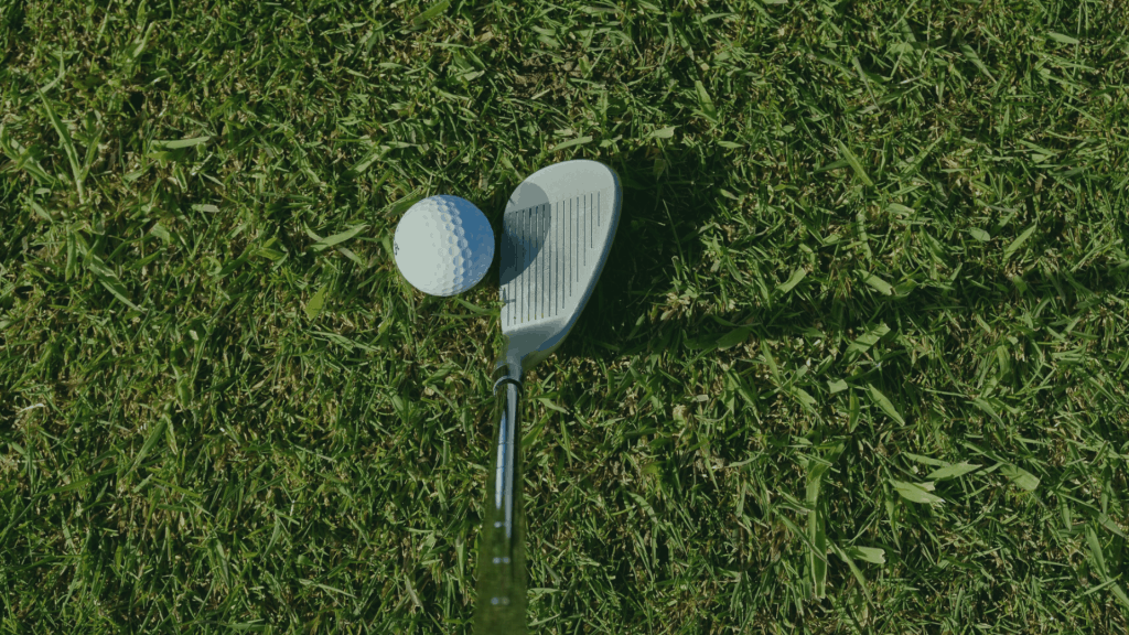 golf iron and ball on the grass