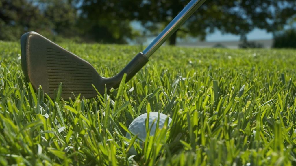 golf iron with ball on grass